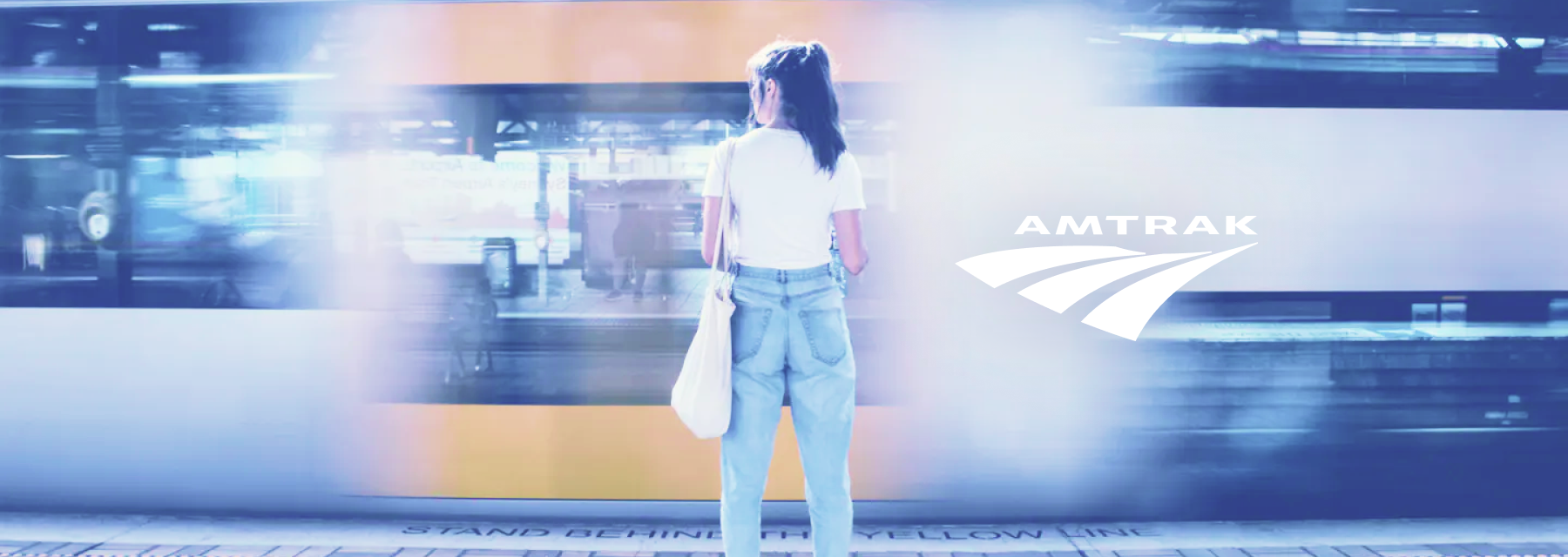 Woman standing in front of passing train with Amtrak logo next to her