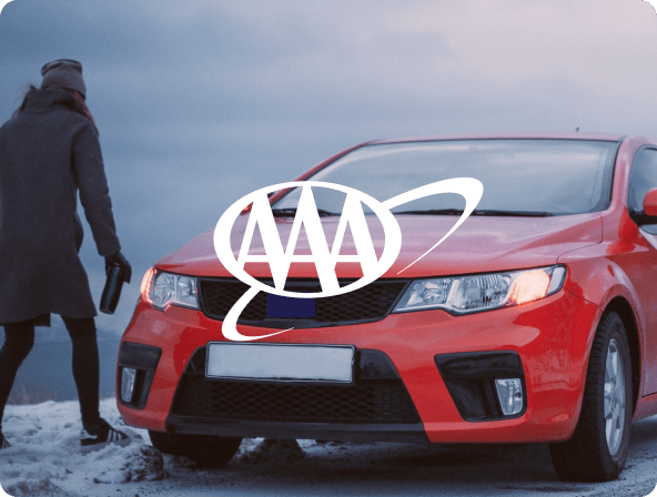 man standing next to red card on snowy road with AAA logo overlay