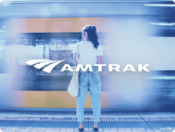 Woman standing in front of passing train with amtrak logo in front.  Themed blue.