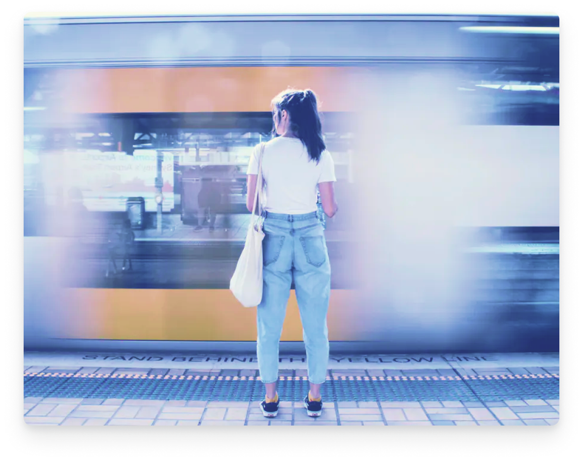 Woman standing in front of a passing traing